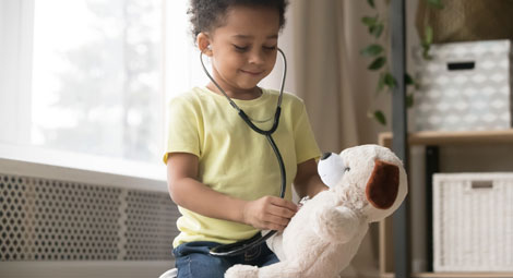 Child with stethoscope and teddy bear